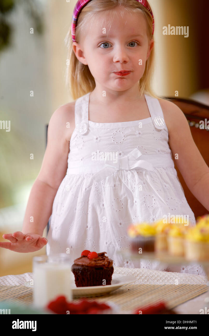 2 year old white girl sneaking a bite of a cupcake.