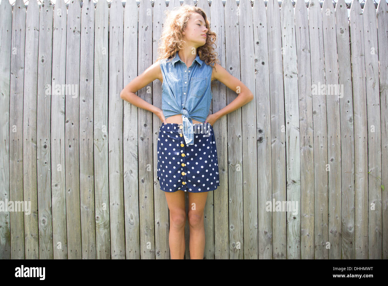 Portrait of teenage girl in front of wooden fence - Stock Image