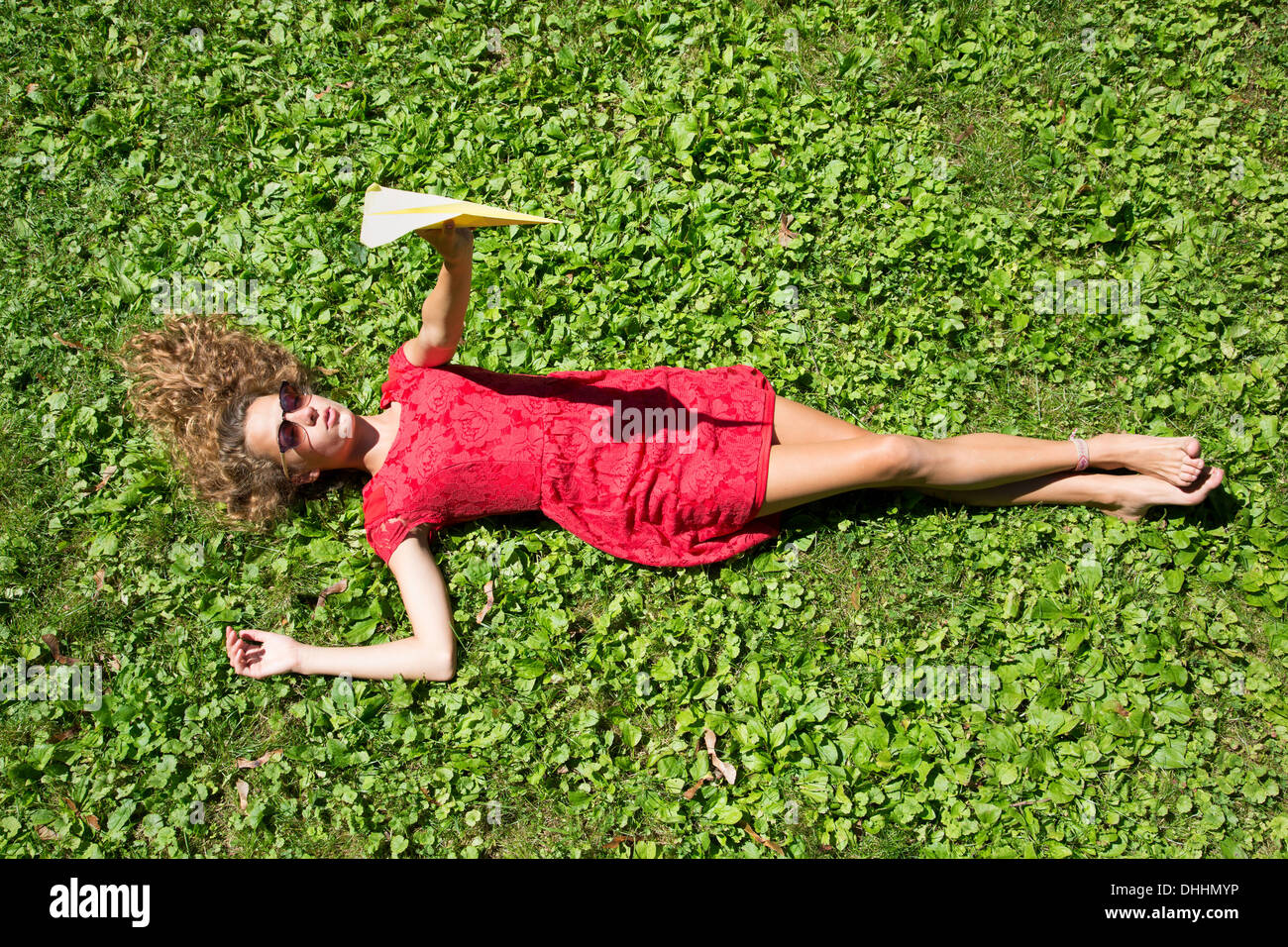 Teenage girl lying on grass holding paper airplane Stock Photo