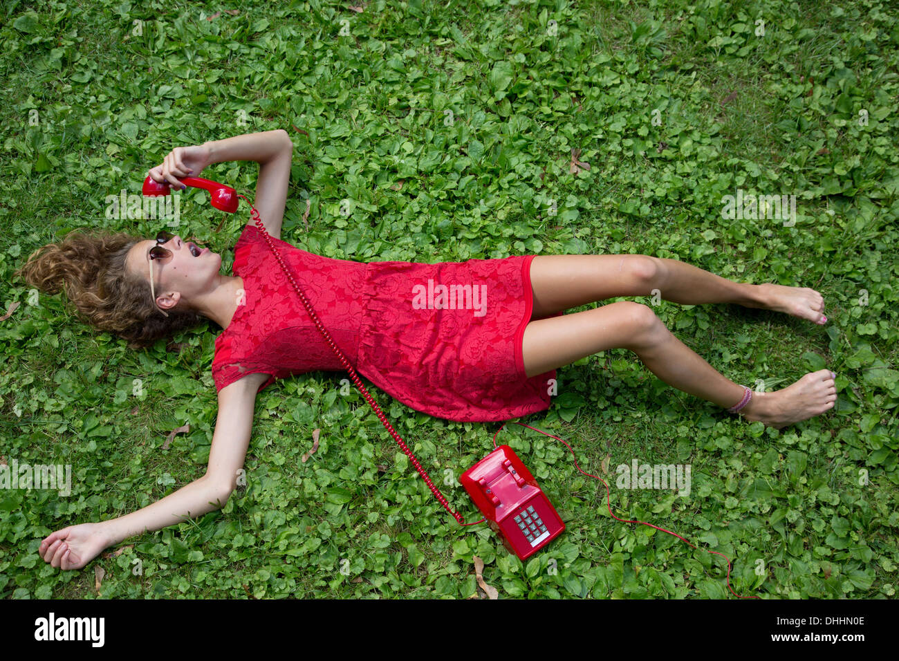 Teenage girl lying on grass with red telephone Stock Photo