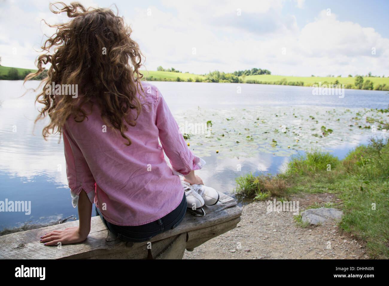 Teenage girl sitting on bench with ice skates - Stock Image