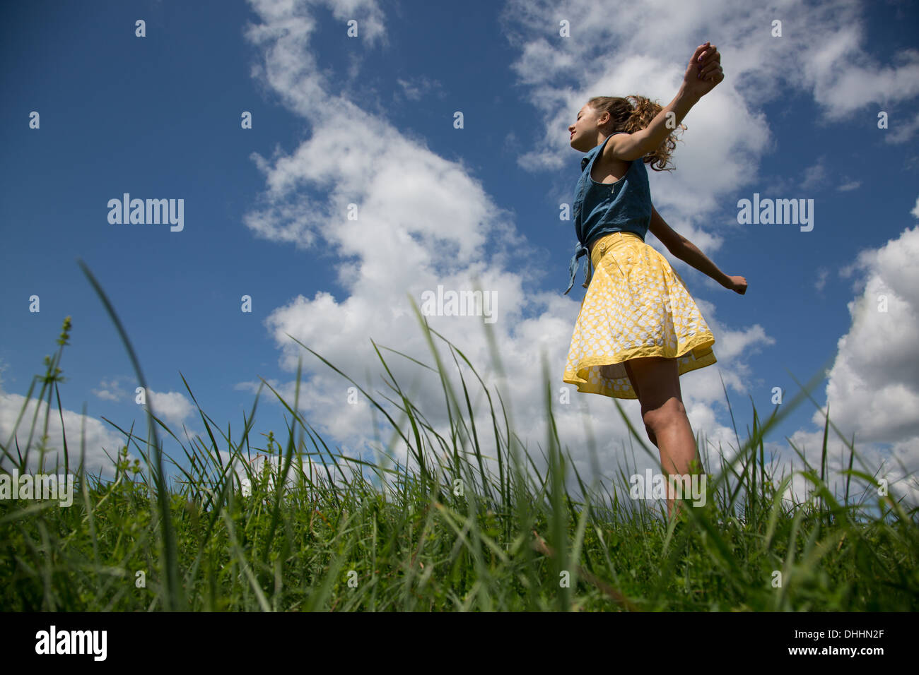 Teenage girl standing with arms outstretched in field - Stock Image