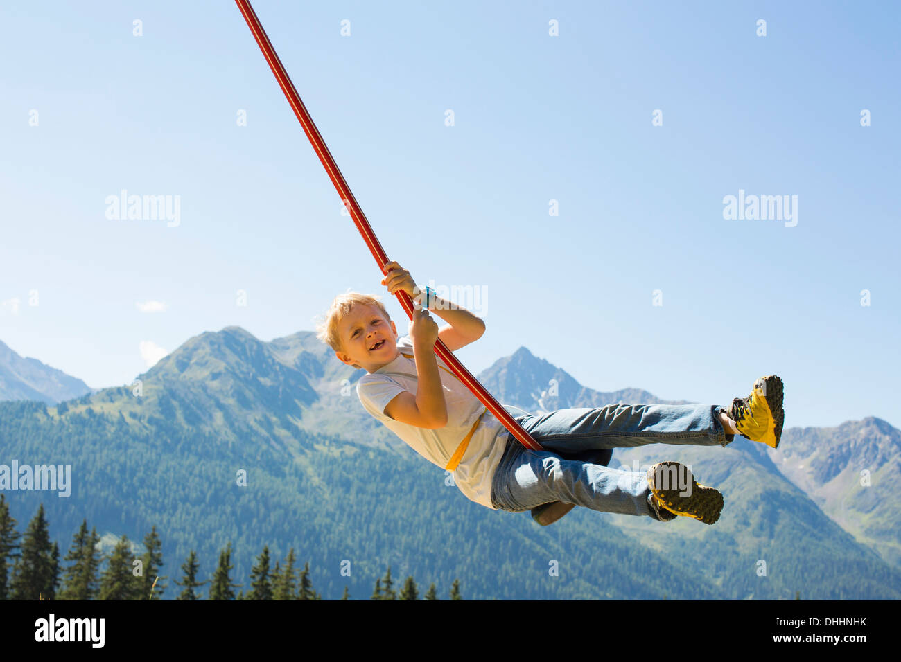Boy playing on swing, Tyrol, Austria - Stock Image