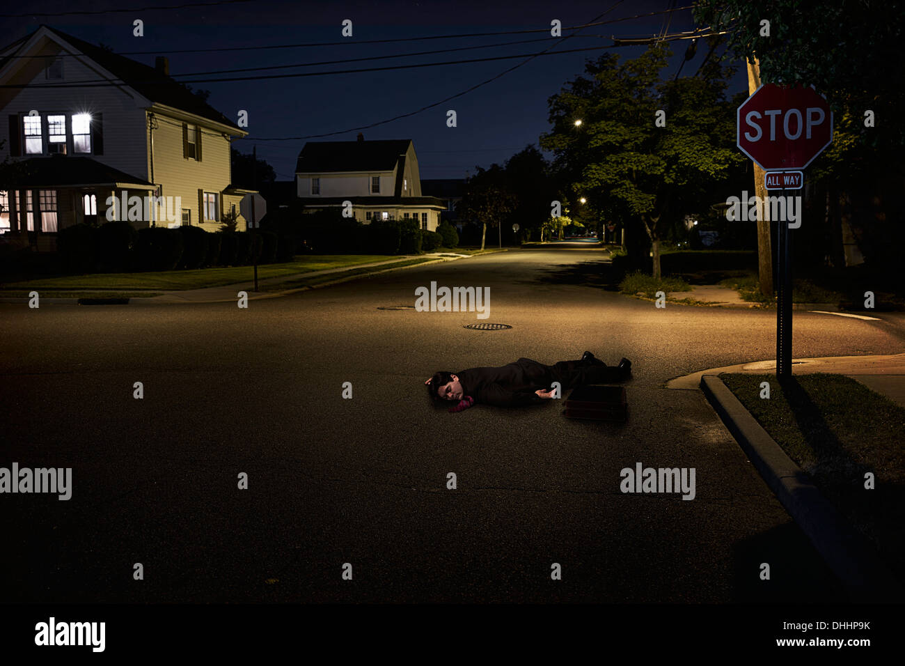 Businessman lying on suburban street unconscious at night - Stock Image