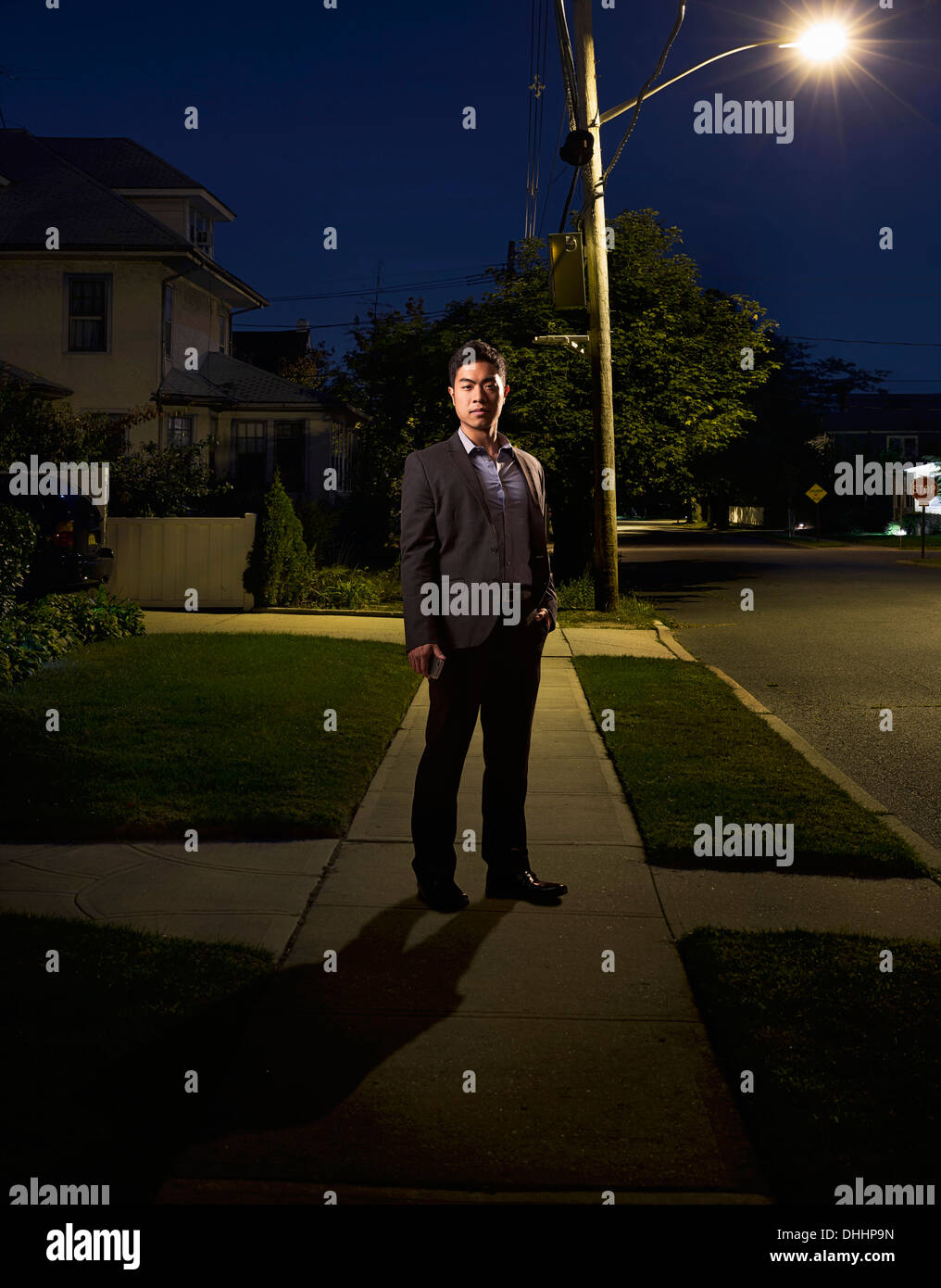 Portrait of business man coming home late at night - Stock Image