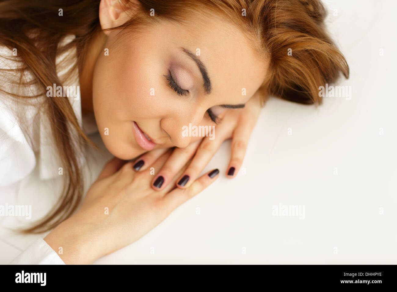 Young businesswoman fallen asleep at office table - Stock Image
