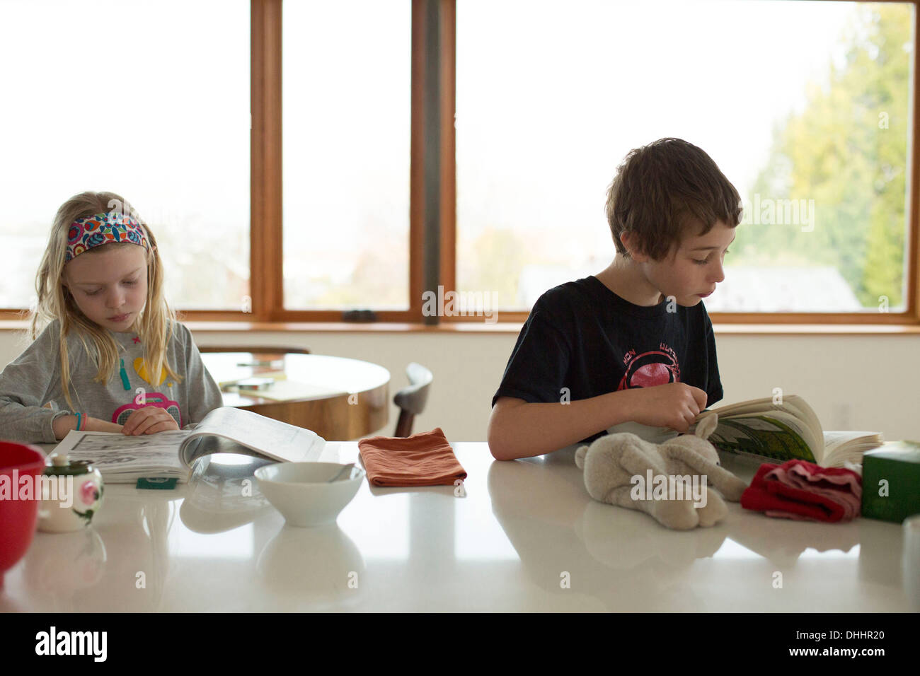 Boy and girl sitting at table reading - Stock Image