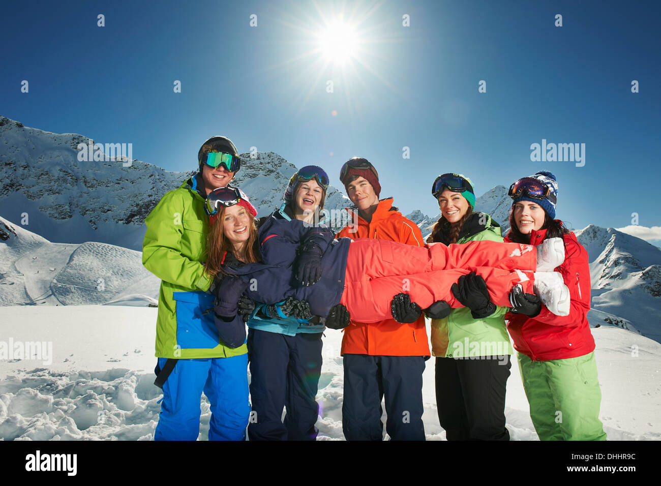 Friends holding woman in snow, Kuhtai, Austria - Stock Image