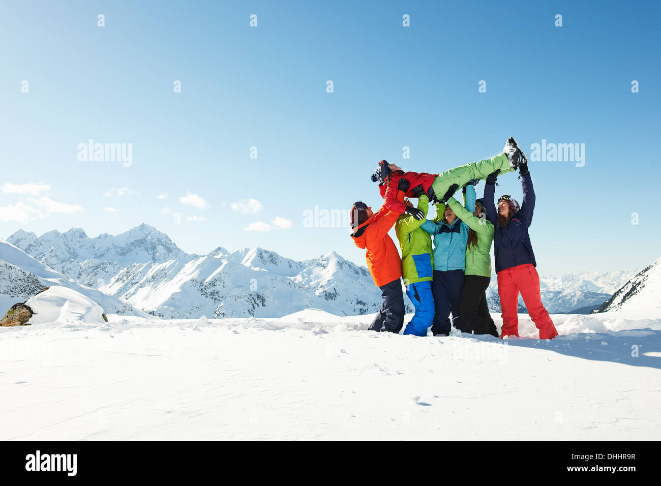 Friends lifting young woman in snow, Kuhtai, Austria Stock Photo