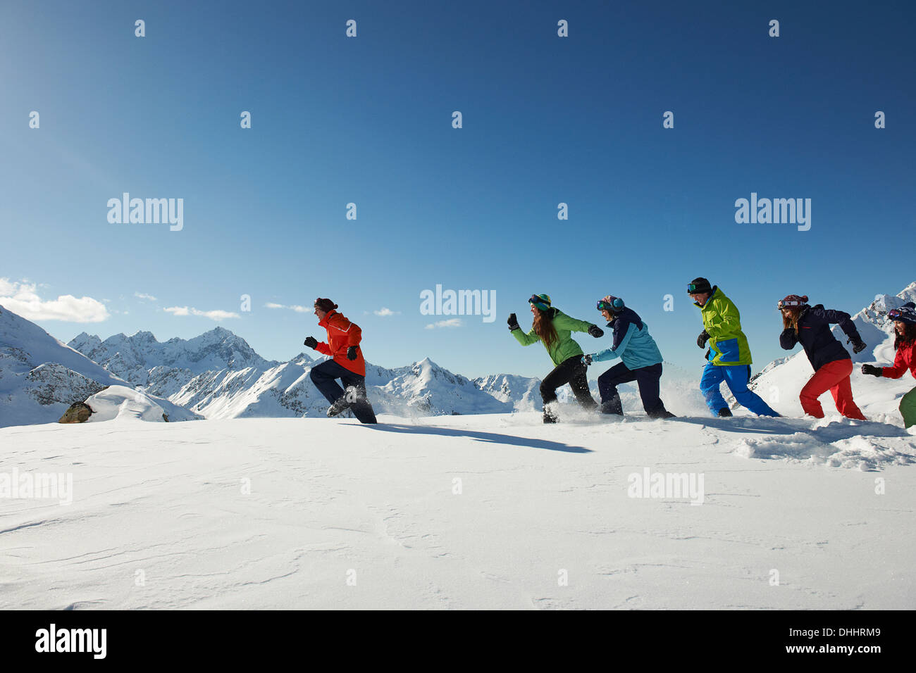 Friends running in snow, Kuhtai, Austria - Stock Image