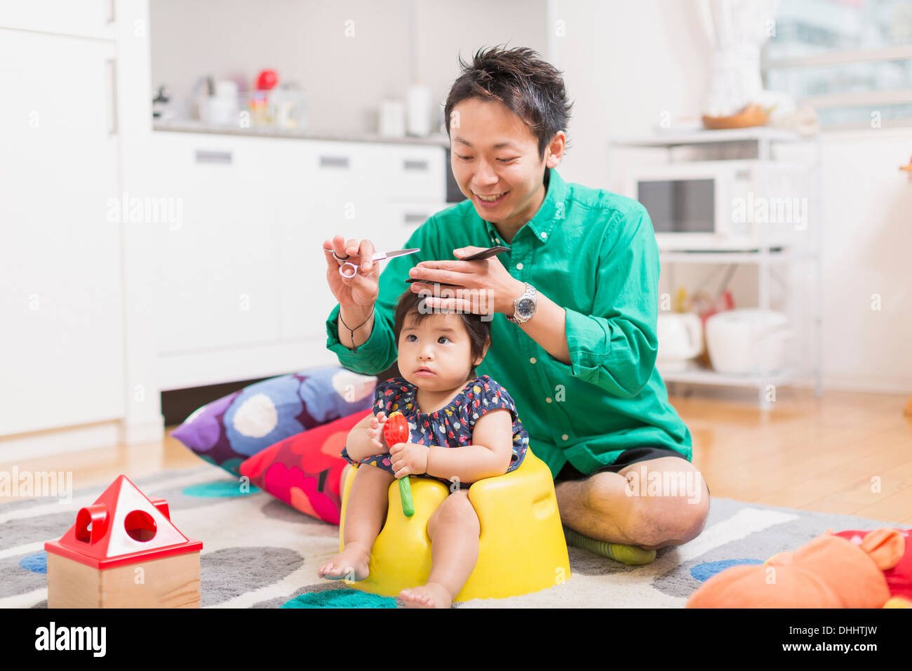 Father cutting baby's hair on floor - Stock Image