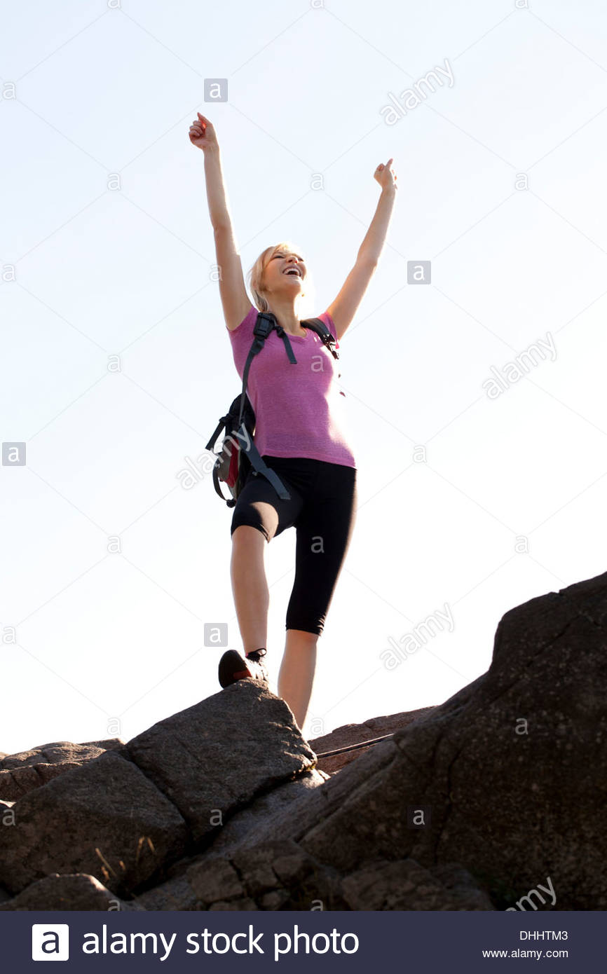 Woman standing at the top of Mont St-Hilaire with arms raised - Stock Image