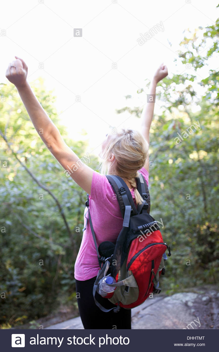 Rear view of woman standing in forest with arms up - Stock Image