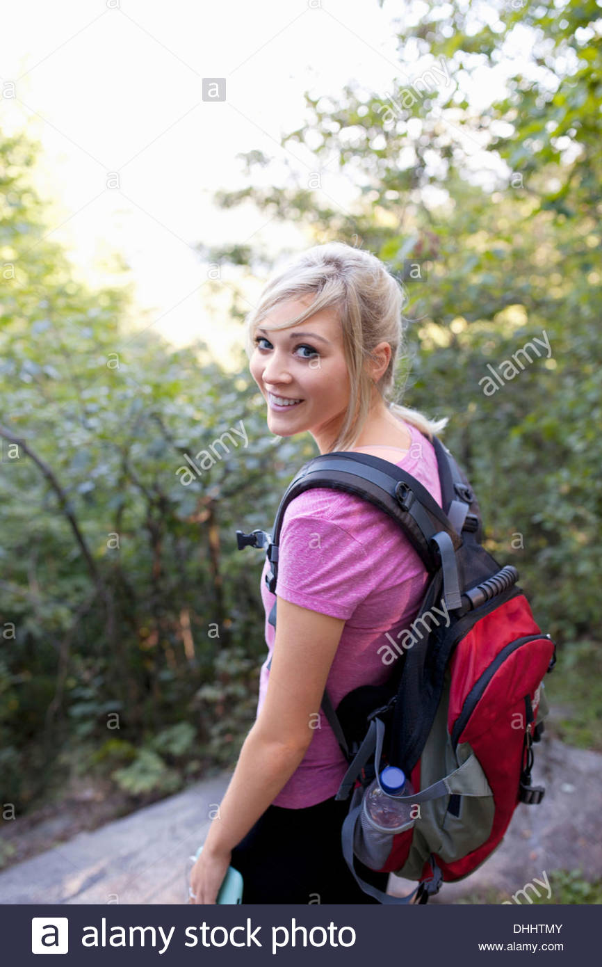 Woman in forest looking at camera - Stock Image
