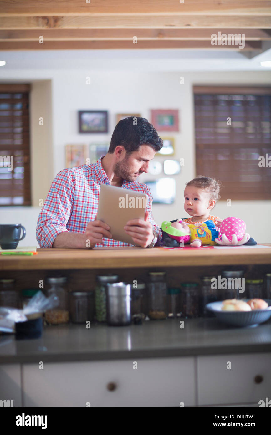 Man and baby sitting at kitchen counter looking at digital tablet - Stock Image