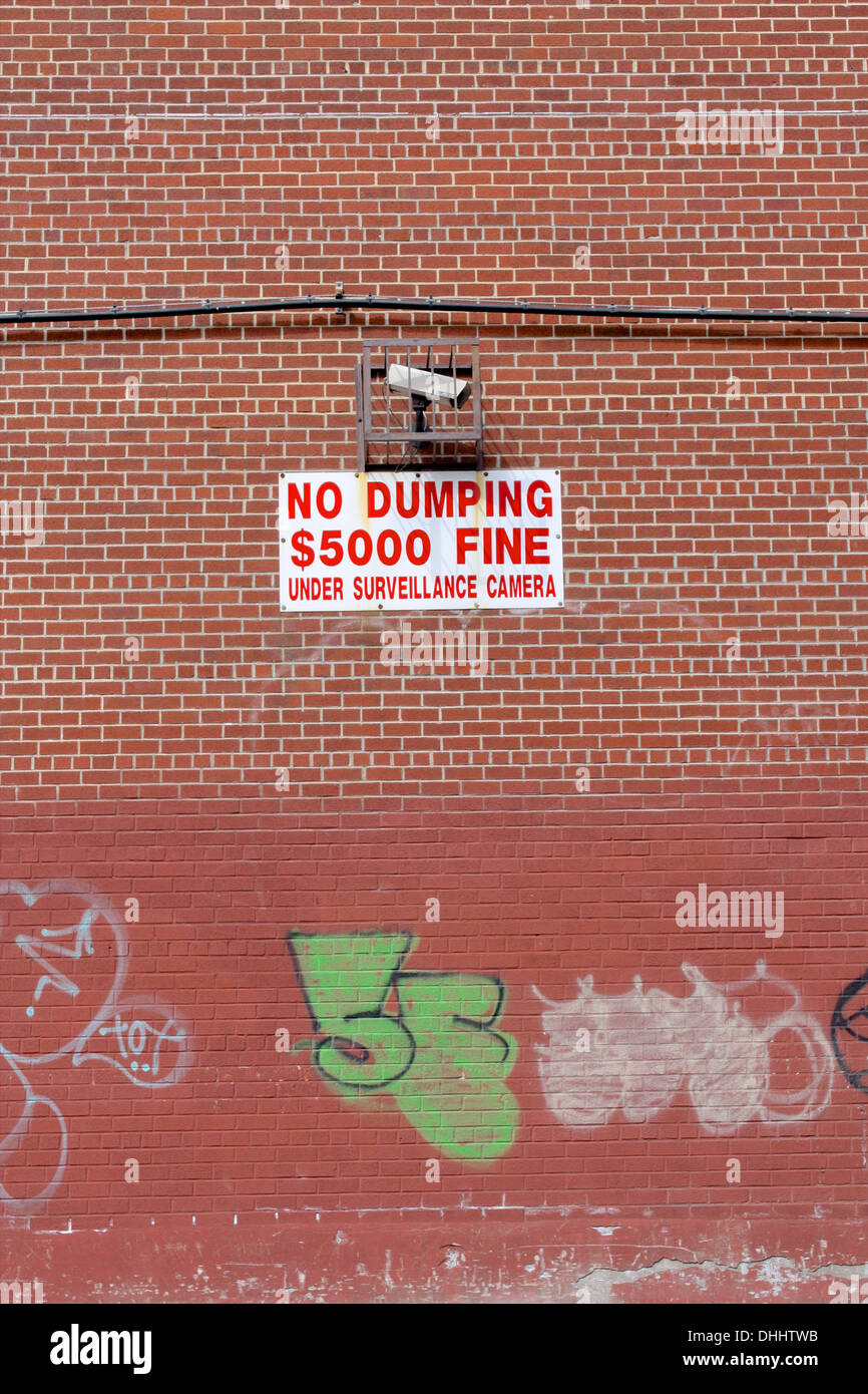 Brick wall with graffiti and a no dumping $5,000 fine sign and surveillance camera in Brooklyn, New York. - Stock Image