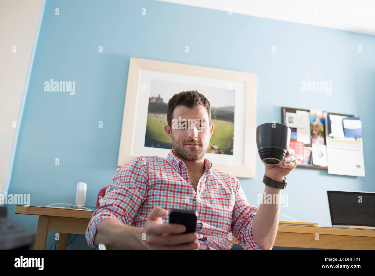 Man sitting at desk with smartphone and coffee cup - Stock Image