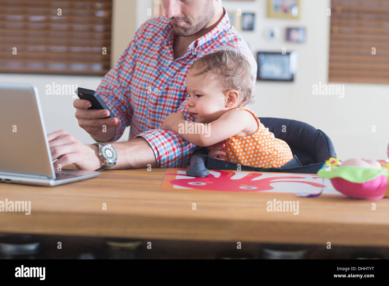 Man working at kitchen counter with baby sitting beside - Stock Image