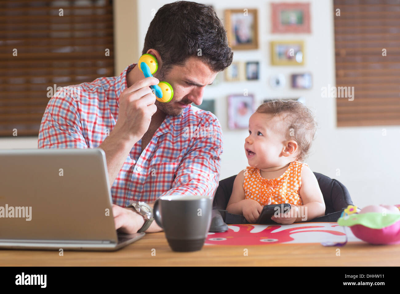 Man and baby sitting at kitchen counter playing with smartphone and toy phone - Stock Image