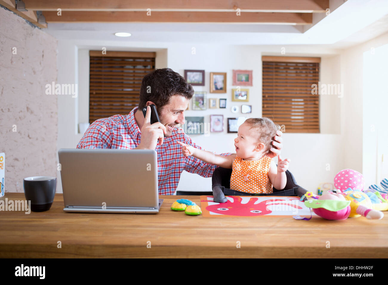 Man and baby sitting at kitchen counter making phone call - Stock Image