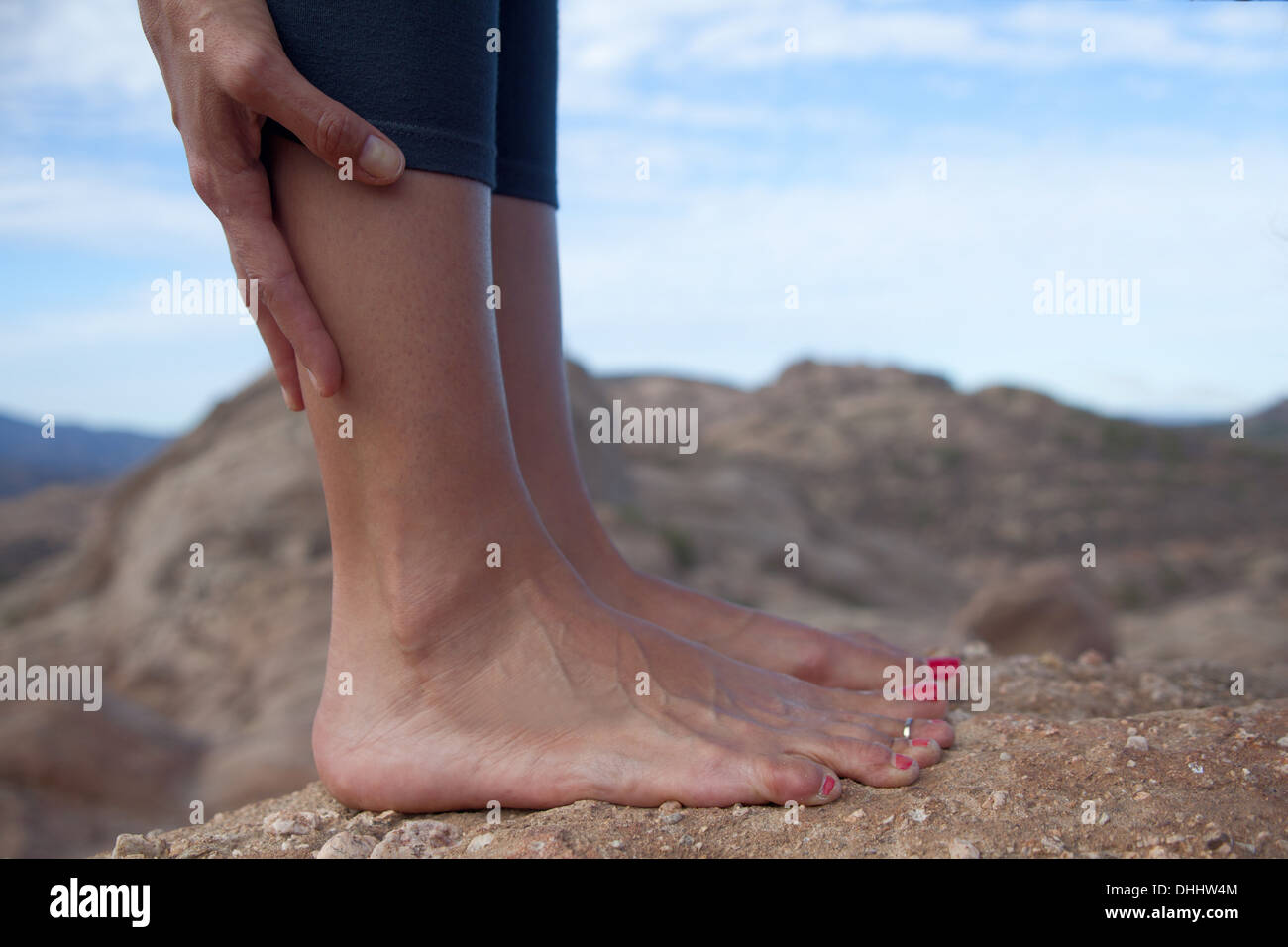 Cropped image of woman's bare feet standing on rocks - Stock Image