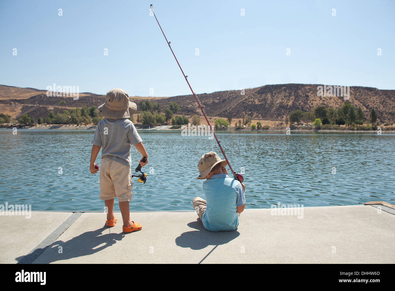 Boys fishing by lake - Stock Image