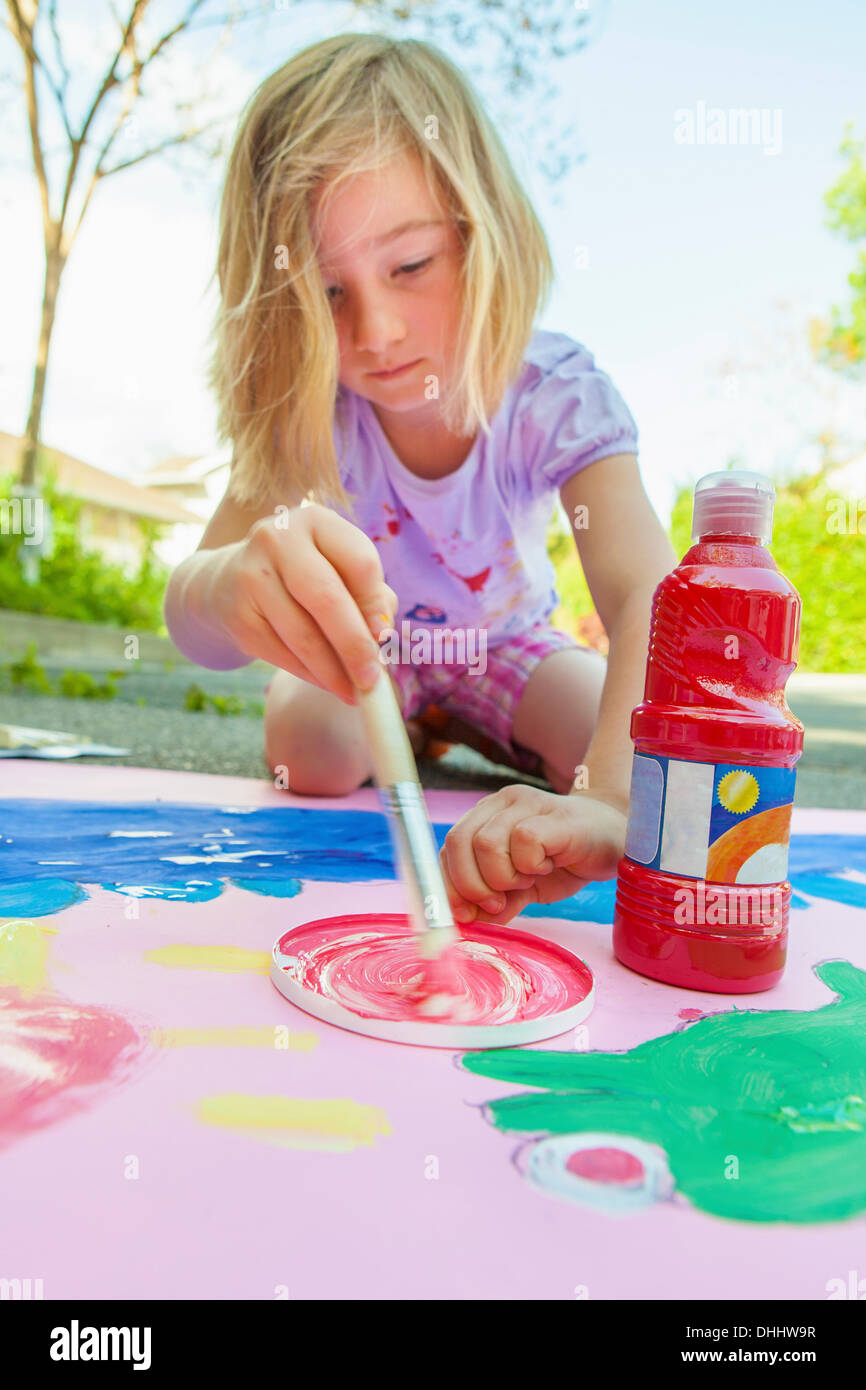 Girl painting with tempera on paper - Stock Image