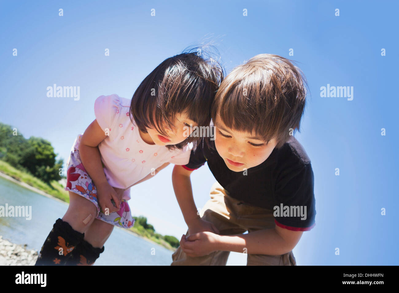 Boy and girl looking down at something - Stock Image