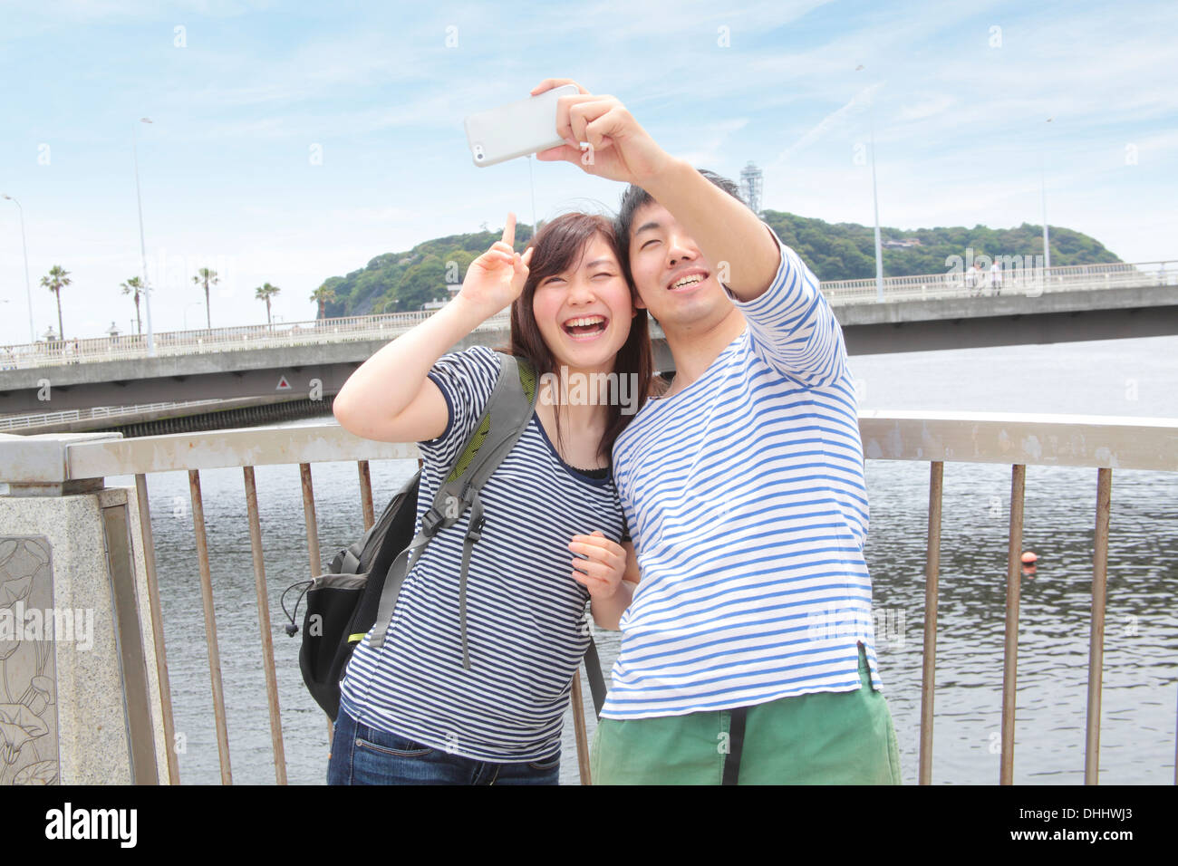 Young couple taking self portrait photograph with smartphone - Stock Image