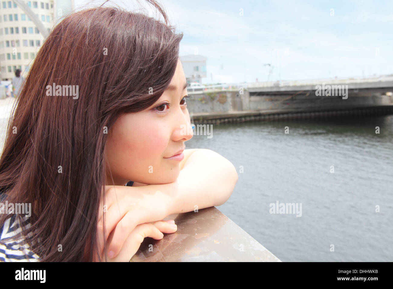 Young woman leaning on railings overlooking river - Stock Image