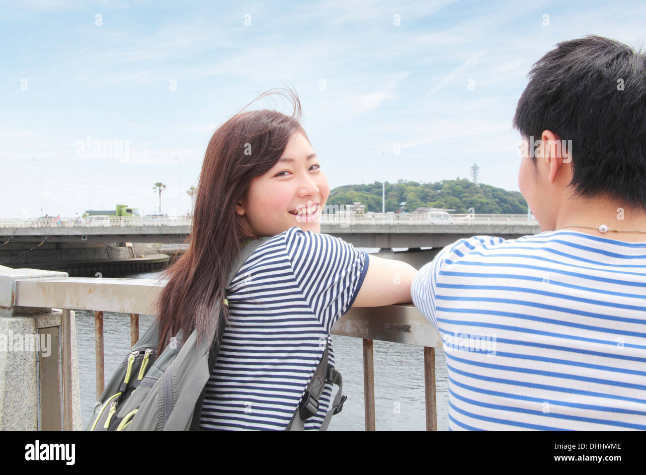 Young couple leaning on railings overlooking river - Stock Image
