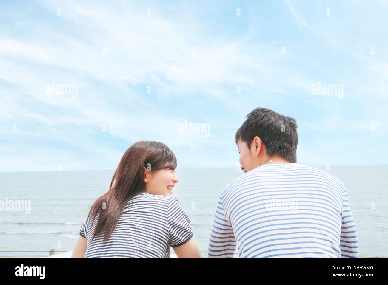 Rear view of couple at coast, face to face and laughing - Stock Image