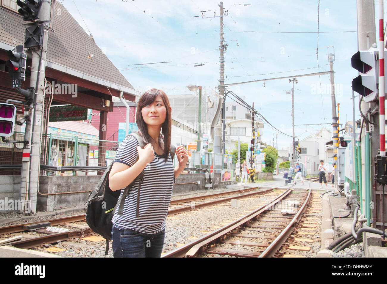 Young woman crossing level crossing over train tracks - Stock Image