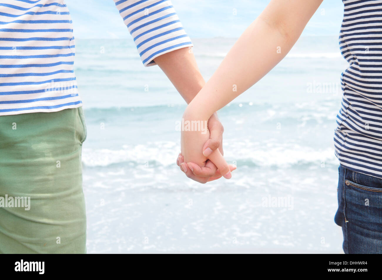 Young couple holding hands in front of sea - Stock Image