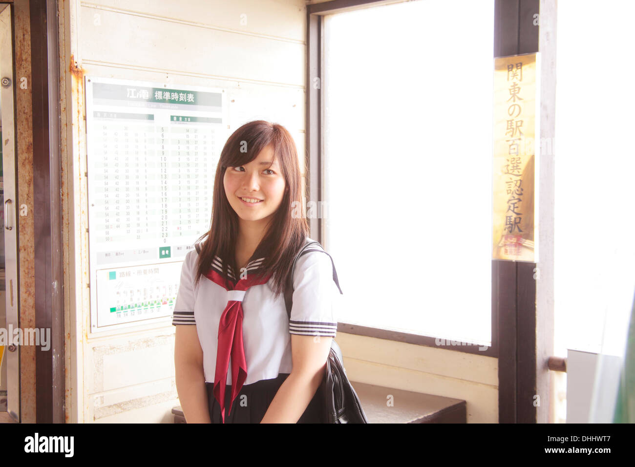 Woman wearing school uniform at train station - Stock Image