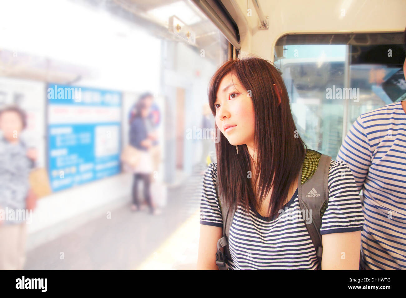 Young woman on train, looking through window - Stock Image