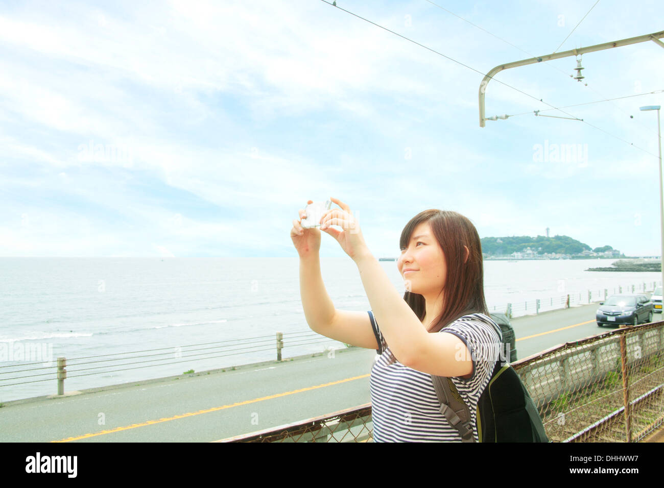 Young woman taking photo at coast with smartphone - Stock Image