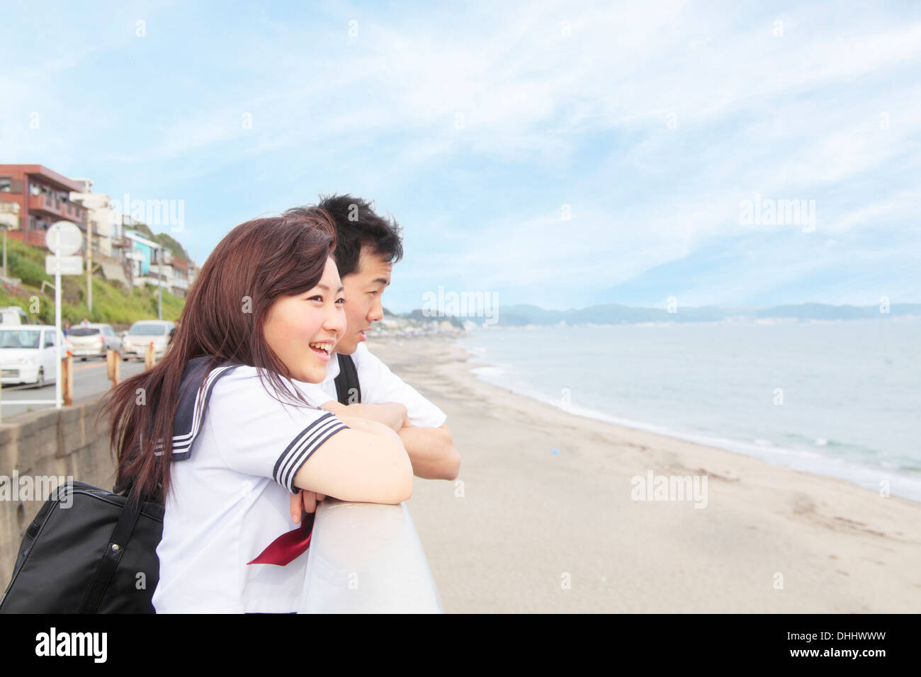Young couple leaning on fence looking at view of sea - Stock Image