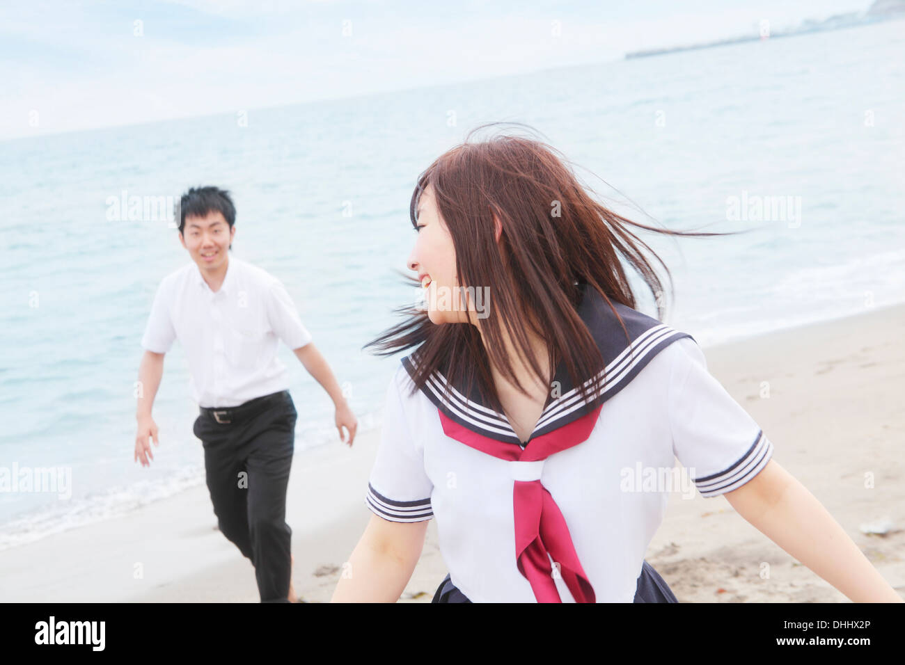 Young couple wearing school uniform running on sandy beach - Stock Image