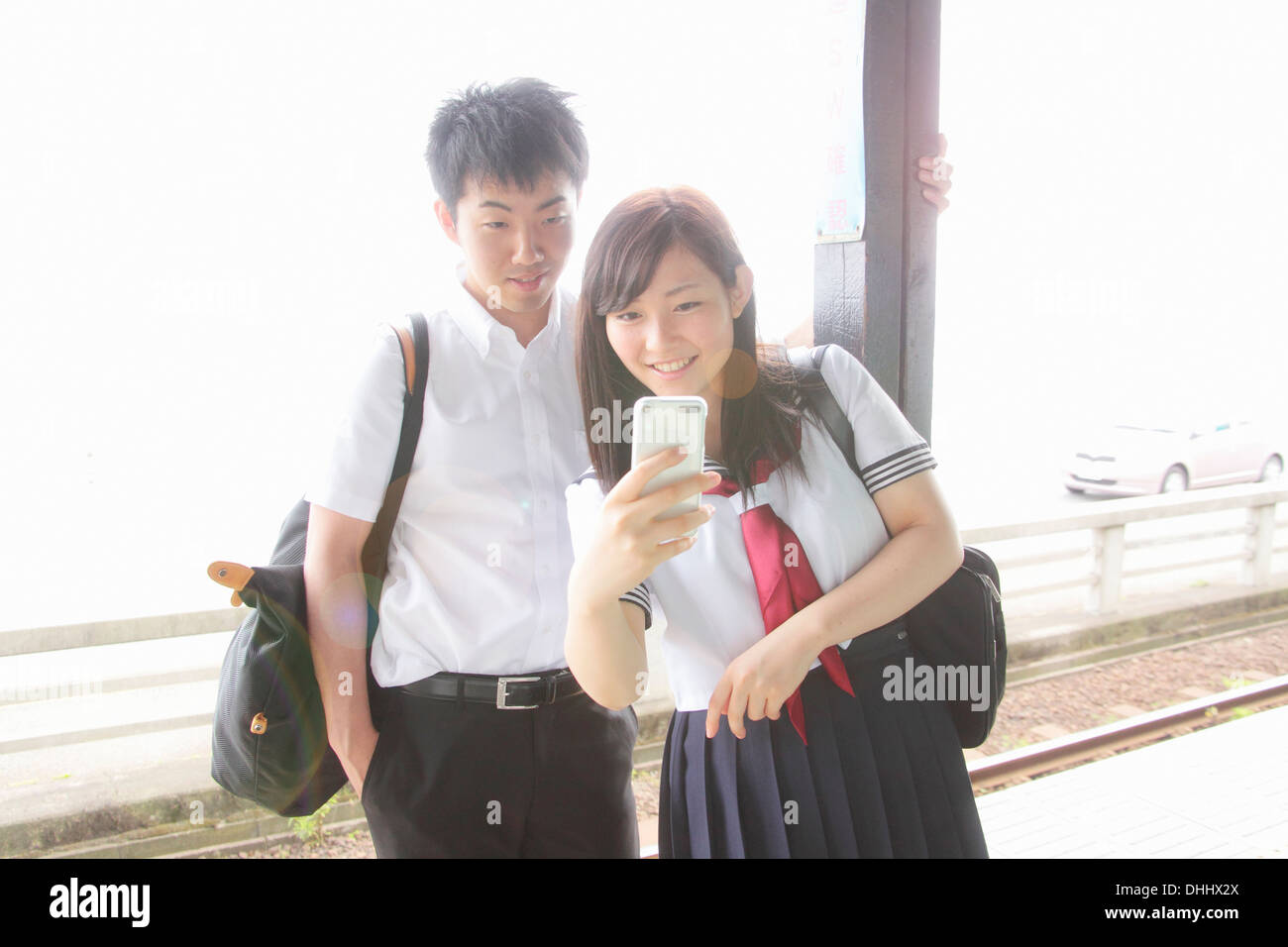 Young couple on railway platform looking at smartphone - Stock Image