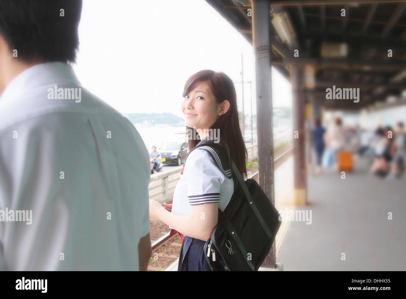 Young woman on railway platform looking at camera - Stock Image