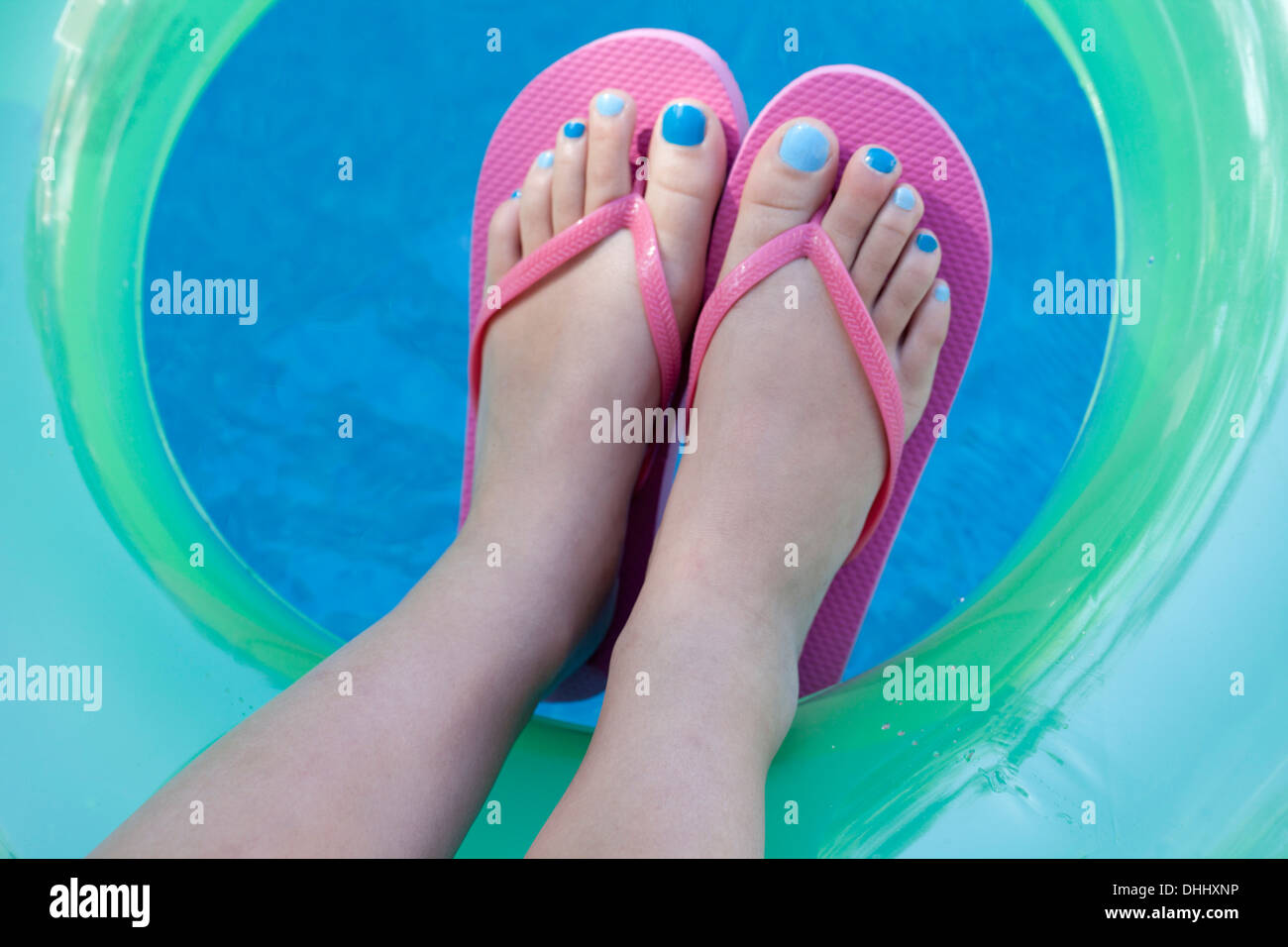 Overhead view of feet with colored nails - Stock Image