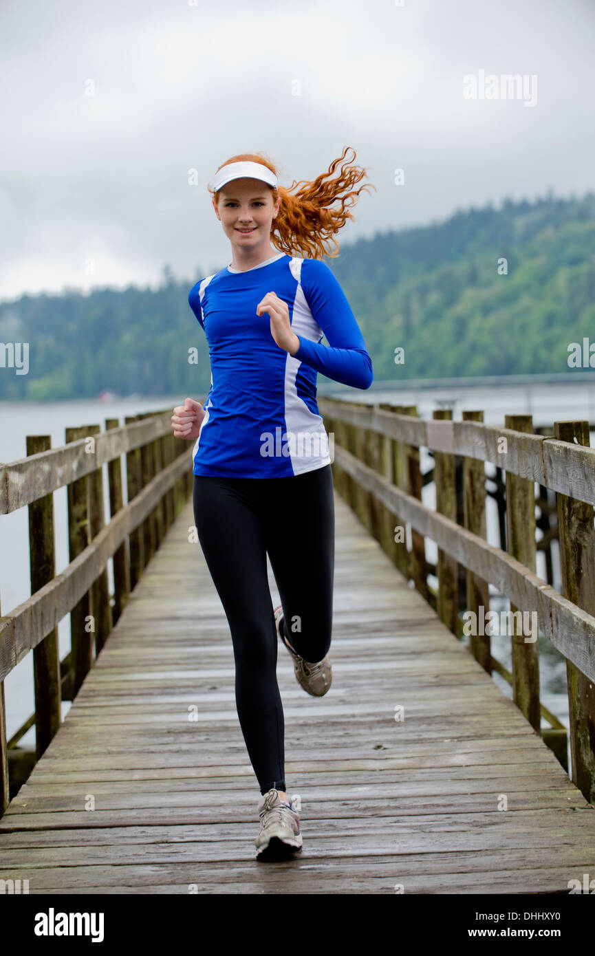 Teenage girl running on pier, Bainbridge Island, Washington, USA - Stock Image