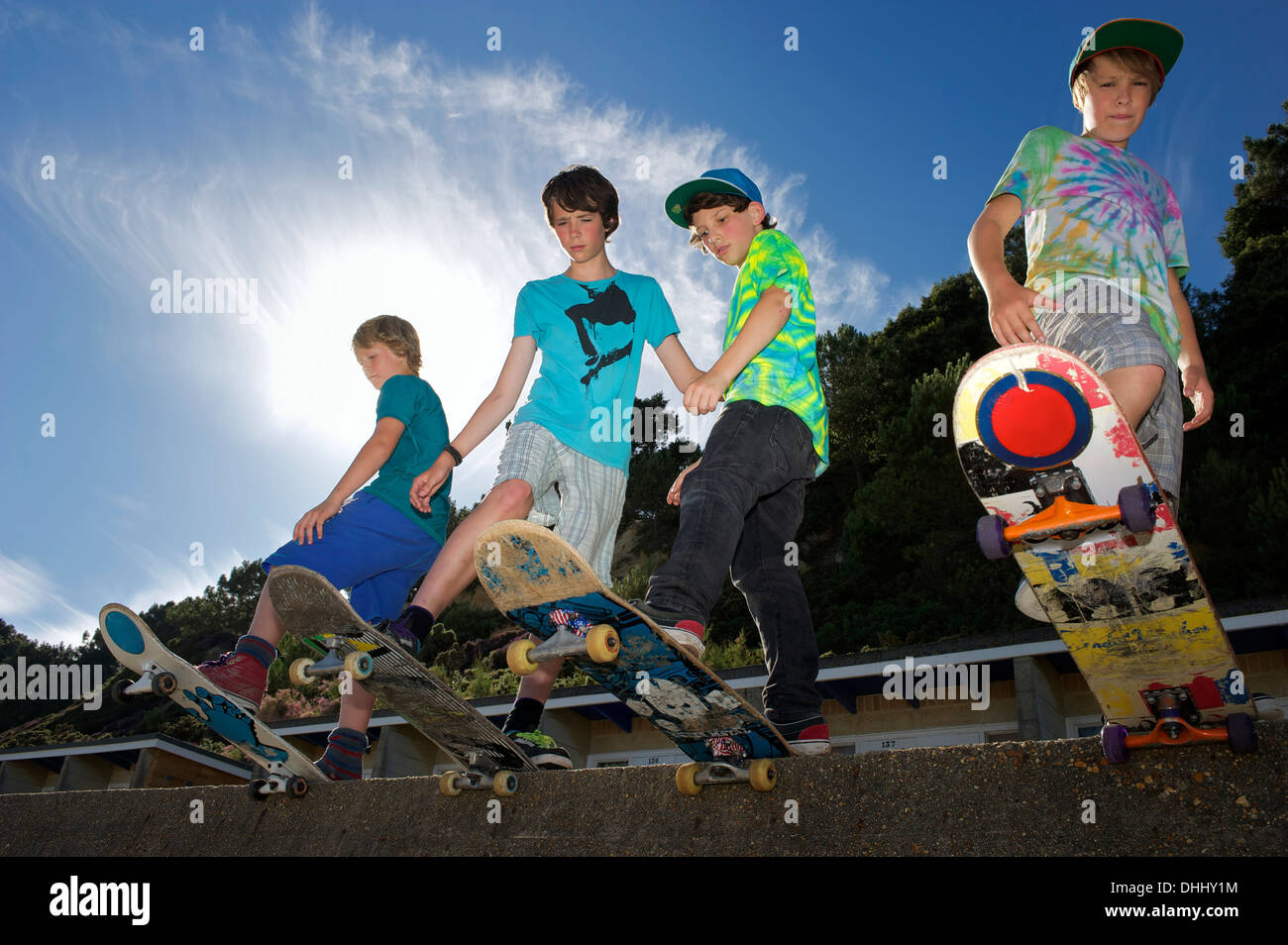 Portrait of four boys on skateboards - Stock Image