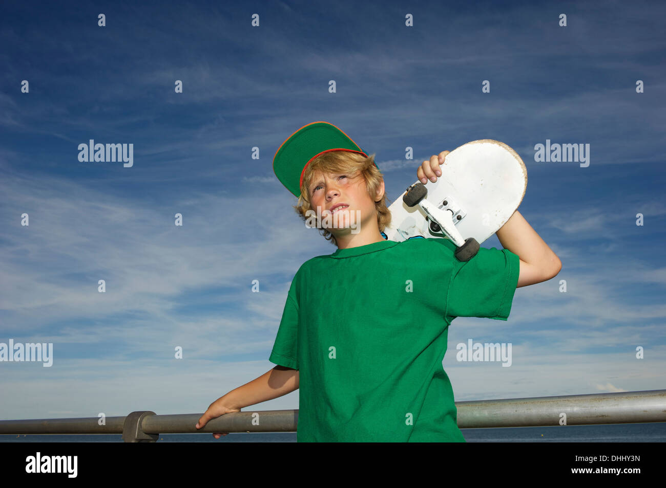 Portrait of boy holding skateboard over shoulder - Stock Image