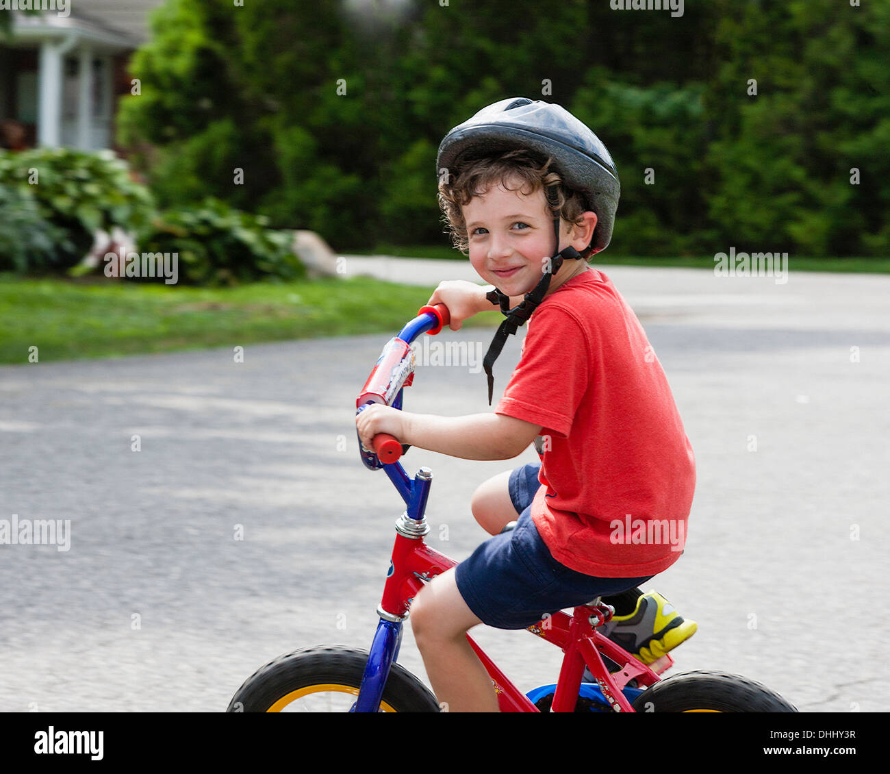 Portrait of young boy riding bicycle on driveway - Stock Image