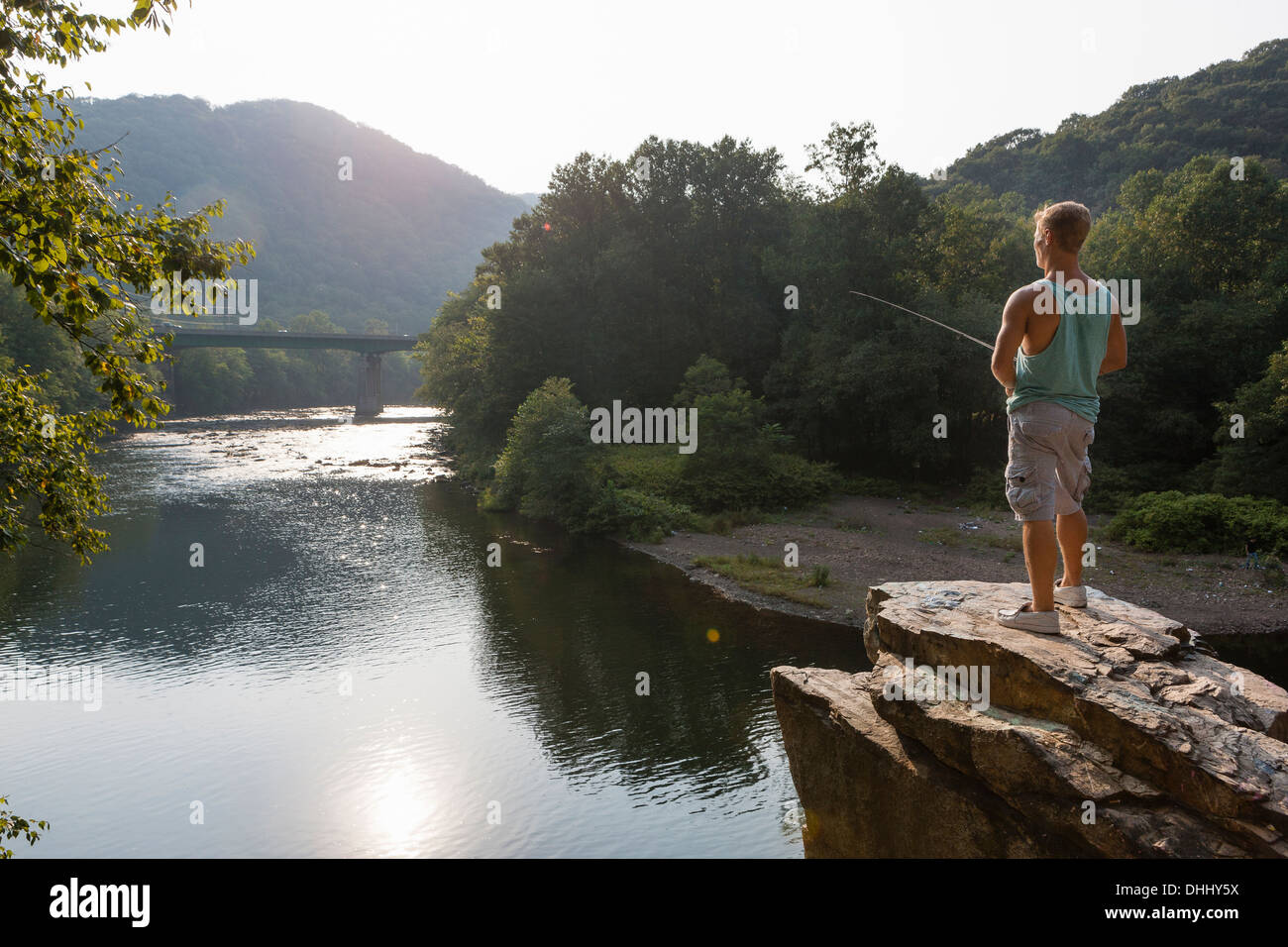 Young man fishing from rock ledge, Hamburg, Pennsylvania, USA - Stock Image