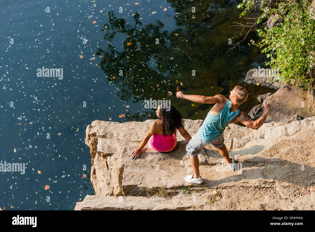 Young couple throwing stones from rock ledge, Hamburg, Pennsylvania, USA - Stock Image