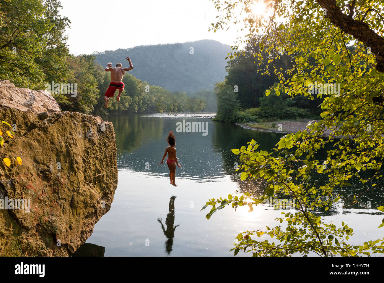 Young couple jumping from rock ledge, Hamburg, Pennsylvania, USA - Stock Image