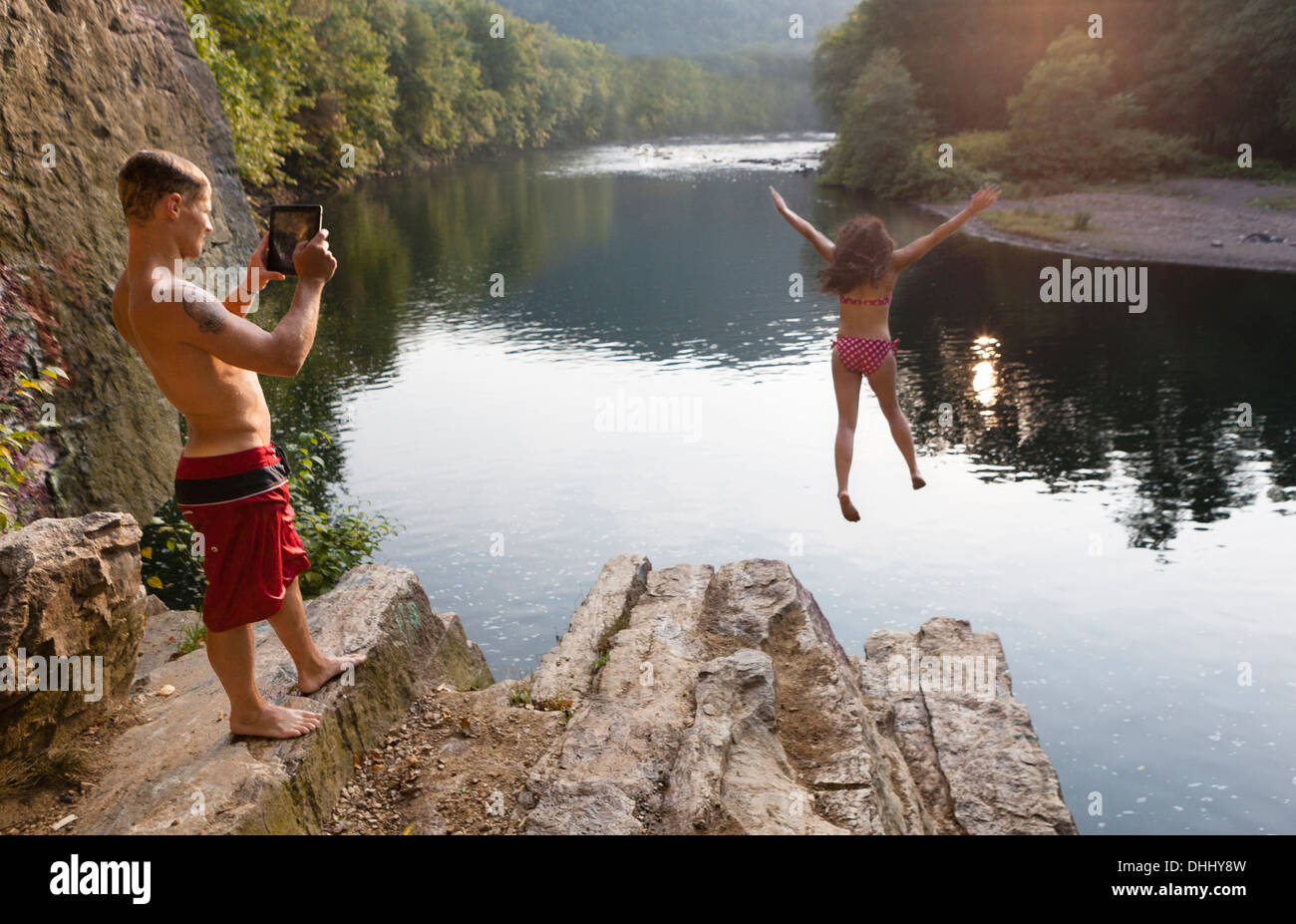 Young couple photographing jump from rock ledge, Hamburg, Pennsylvania, USA - Stock Image